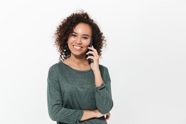 Portret van een vrij vrolijk, casual afrikaans meisje dat geïsoleerd over een witte muur staat en op een mobiele telefoon praat