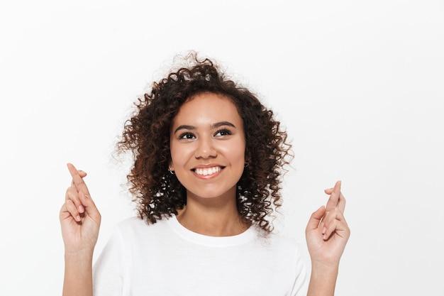 Portret van een vrij vrolijk, casual afrikaans meisje dat geïsoleerd over een witte muur staat, met de vingers gekruist voor geluk