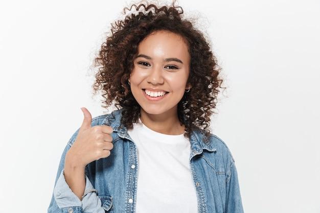 Portret van een vrij vrolijk casual afrikaans meisje dat geïsoleerd staat over een witte muur, duimen omhoog