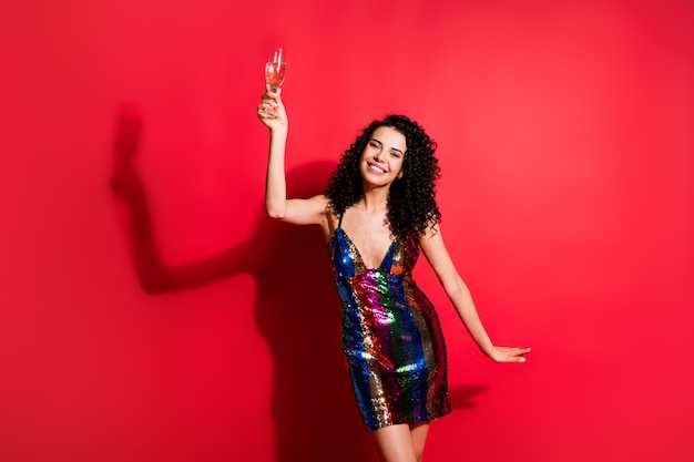 Portret van een vrij vrolijk meisje met golvend haar dat wijn drinkt, feestelijk dansend geïsoleerd op een levendige rode kleurachtergrond
