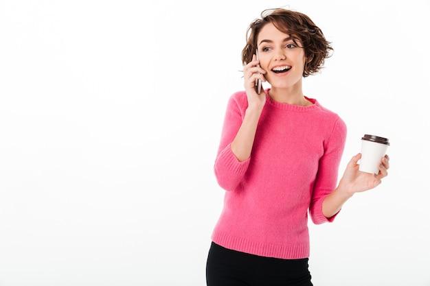 Portret van een vrolijk aantrekkelijk meisje dat op mobiele telefoon spreekt