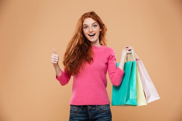 Portret van een vrolijk aantrekkelijk roodharigemeisje met het winkelen zakken