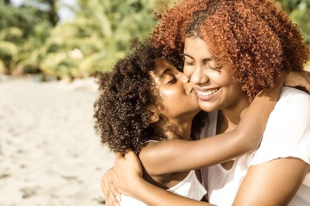 Portret van een vrolijk afrikaans-amerikaans meisje dat een glimlachende jonge zwarte moeder op zonnige dag kust