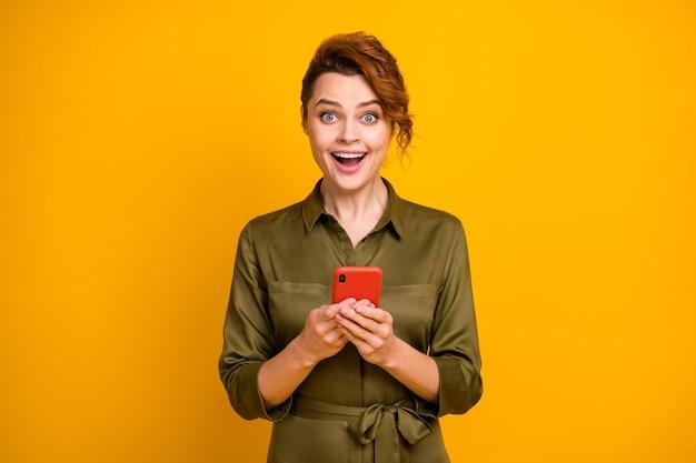 Portret van een vrolijk, blij verbaasd meisje dat een gek gezicht van de telefoon gebruikt