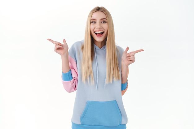 Portret van een vrolijk blond meisje dat hulp vraagt bij het nemen van beslissingen, met de vingers naar links en rechts wijst, producten zijwaarts laat zien