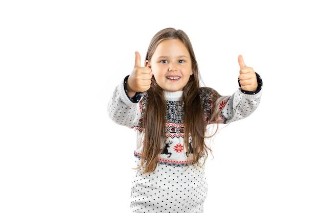 Portret van een vrolijk charmant meisje in een witte kersttrui met rendieren die een duim omhoog iso...