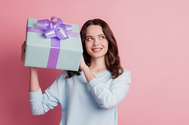 Portret van een vrolijk geïnteresseerd meisje dat de huidige doos vasthoudt, denk dat je lege ruimte ziet