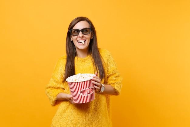 Portret van een vrolijk gelukkig jong meisje in een 3d imax-bril die filmfilm kijkt en popcorn eet uit een emmer geïsoleerd op een felgele achtergrond. mensen oprechte emoties in de bioscoop, lifestyle concept.