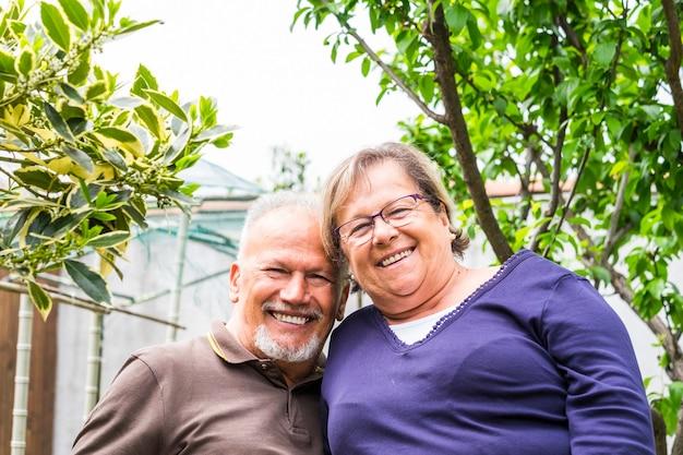 Portret van een vrolijk, gelukkig ouder echtpaar dat lacht en samen plezier heeft in de tuin - een gepensioneerde levensstijl voor aardige kaukasische mensen buiten -