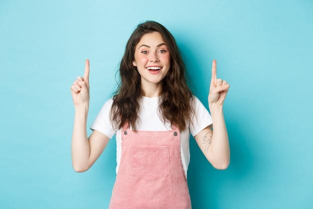 Portret van een vrolijk glamourmeisje dat gelukkig lacht, opgewonden kijkt en met de vingers omhoog wijst, advertenties toont, zomerkleren draagt, blauwe achtergrond