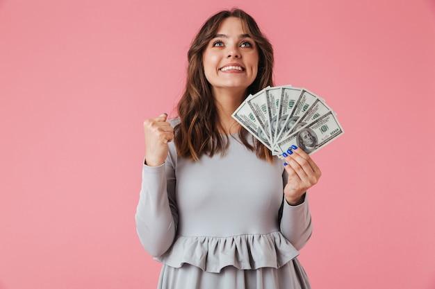 Portret van een vrolijk jong het geldbankbiljetten van de meisjesholding