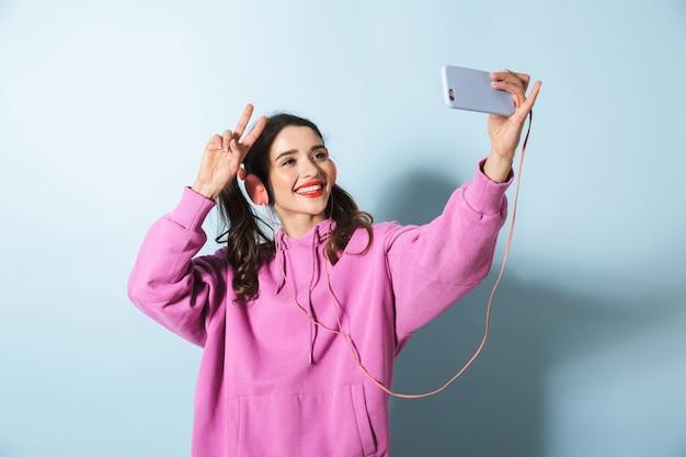 Portret van een vrolijk jong meisje dat hoodie draagt die zich over blauw bevindt, hoofdtelefoons draagt, die een selfie neemt