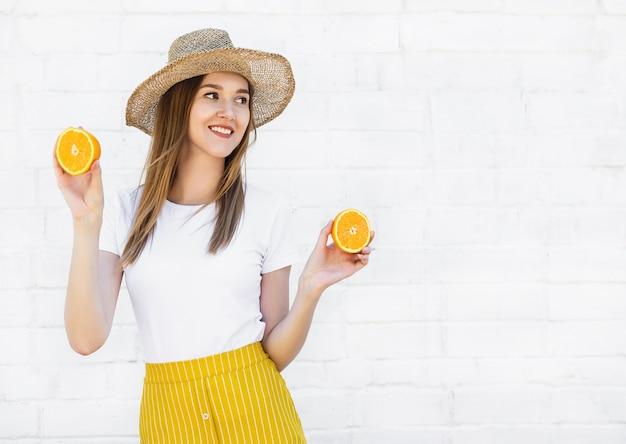 Portret van een vrolijk jong meisje dat in hoed twee plakken van sinaasappel op witte muur houdt