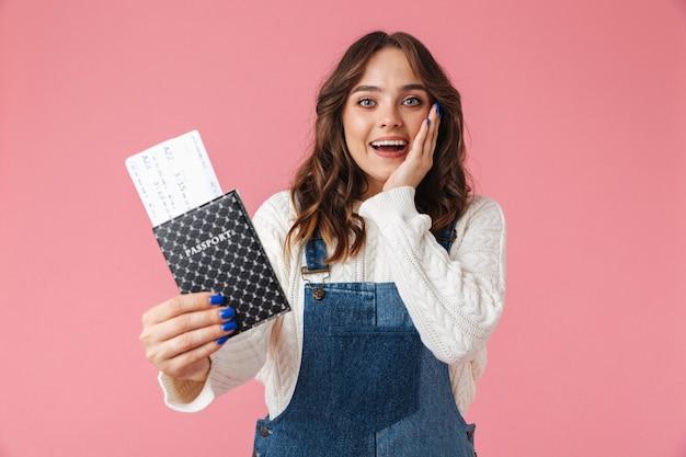 Portret van een vrolijk jong meisje dat paspoort toont