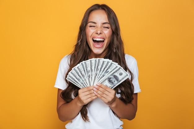 Portret van een vrolijk jong meisje met lang donkerbruin haar dat zich over gele muur bevindt, geldbankbiljetten houdt