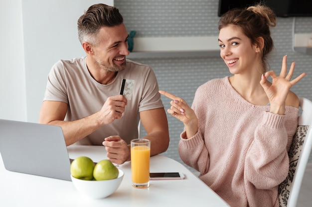 Portret van een vrolijk jong paar dat online winkelt