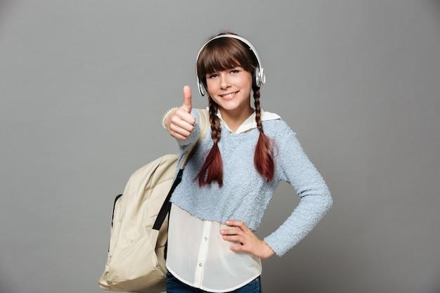 Portret van een vrolijk jong schoolmeisje met rugzak