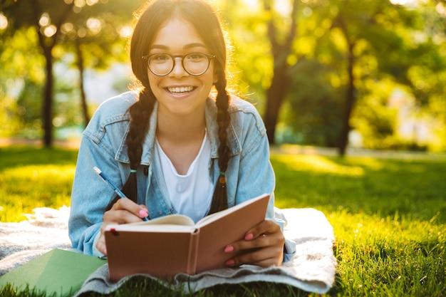 Portret van een vrolijk jong studentenmeisje met een bril die buiten in het natuurpark zit en notities schrijft die een boek lezen. camera kijken.