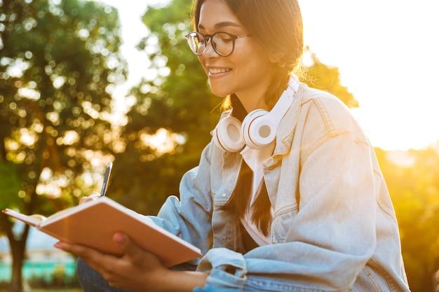 Portret van een vrolijk jong studentenmeisje met een bril die buiten in het natuurpark zit, naar muziek luistert met een koptelefoon en notities schrijft