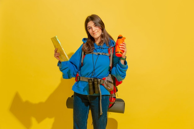 Portret van een vrolijk jong toeristenmeisje met zak en verrekijker dat op gele studiomuur wordt geïsoleerd