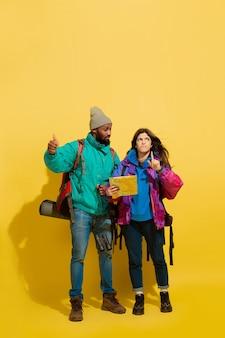 Portret van een vrolijk jong toeristenpaar met zakken dat op gele studiomuur wordt geïsoleerd
