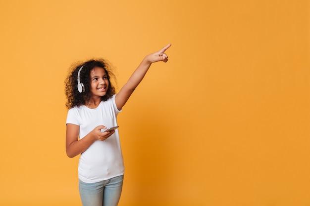 Portret van een vrolijk klein afrikaans meisje dat aan muziek luistert