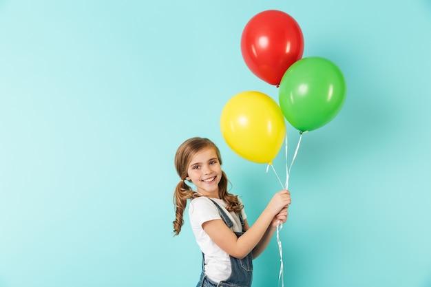 Portret van een vrolijk klein meisje geïsoleerd over blauwe muur, met een bos kleurrijke luchtballonnen