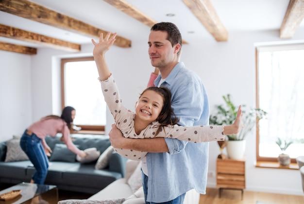 Portret van een vrolijk klein meisje met vader binnenshuis, die plezier heeft.