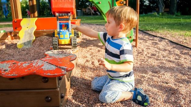 Portret van een vrolijk lachend jongetje dat zand in speelgoedvrachtwagen met aanhanger giet. kinderen spelen en spelen op de speelplaats in het park