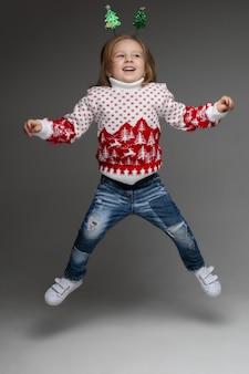 Portret van een vrolijk lachend kind in een trui met winterornament, jeans en schoenen met een grappig kerstboomhoofdaccessoire dat op de muur springt.
