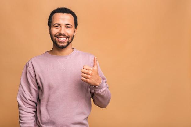 Portret van een vrolijk lachende jonge man gekleed in casual geïsoleerd tegen beige, duimen opdagen.