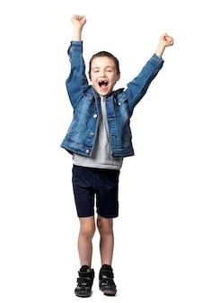 Portret van een vrolijk lachende jongen in denim jasje met vuisten en vreugde over zijn prestaties en overwinning op wit