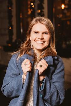 Portret van een vrolijk meisje breed lachend naar de camera buitenshuis.