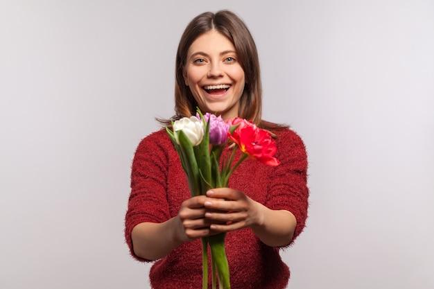 Portret van een vrolijk meisje dat bloemenboeket geeft aan de camera en opgewonden glimlacht.