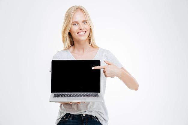 Portret van een vrolijk meisje dat het lege laptop computerscherm toont dat op een witte achtergrond wordt geïsoleerd