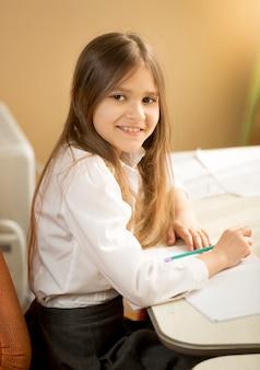 Portret van een vrolijk meisje dat huiswerk doet achter een bureau