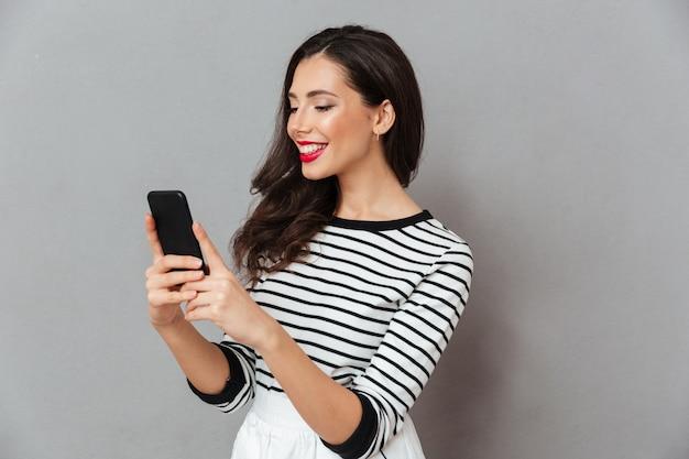 Portret van een vrolijk meisje dat mobiele telefoon bekijkt