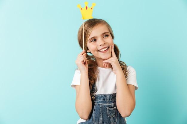 Portret van een vrolijk meisje geïsoleerd over blauwe muur, met een kleine kroon