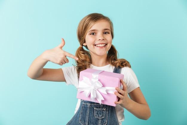 Portret van een vrolijk meisje geïsoleerd over blauwe muur, met huidige doos