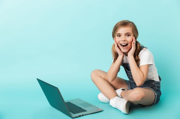 Portret van een vrolijk meisje geïsoleerd over blauwe muur, studerend met laptopcomputer