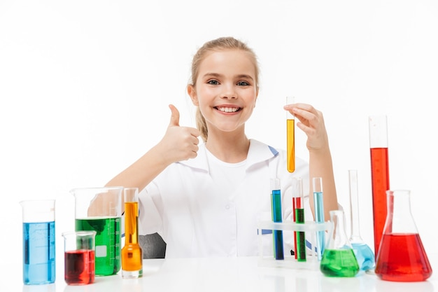 Portret van een vrolijk meisje in een witte laboratoriumjas die chemische experimenten maakt met veelkleurige vloeistof in reageerbuizen geïsoleerd over een witte muur