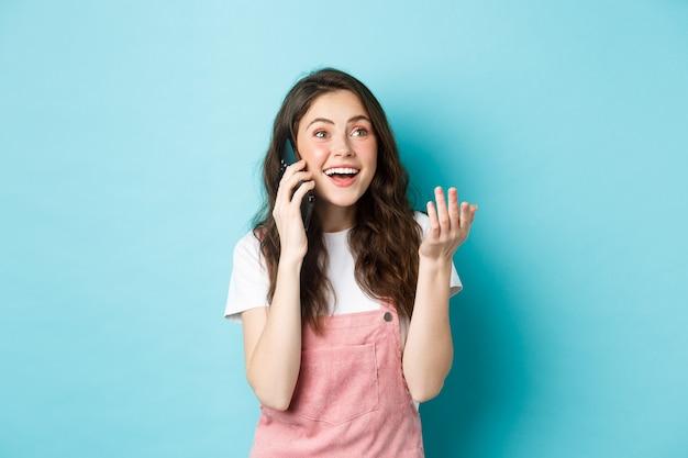 Portret van een vrolijk modern meisje dat aan de telefoon praat, gebaren maakt en er gelukkig uitziet, glimlachend in de camera, chat met een vriend op smartphone, staande over blauwe achtergrond.