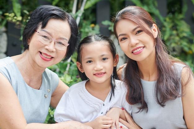 Portret van een vrolijk mooi klein meisje, haar moeder en grootmoeder die tijd buitenshuis doorbrengen in de achtertuin of in het park