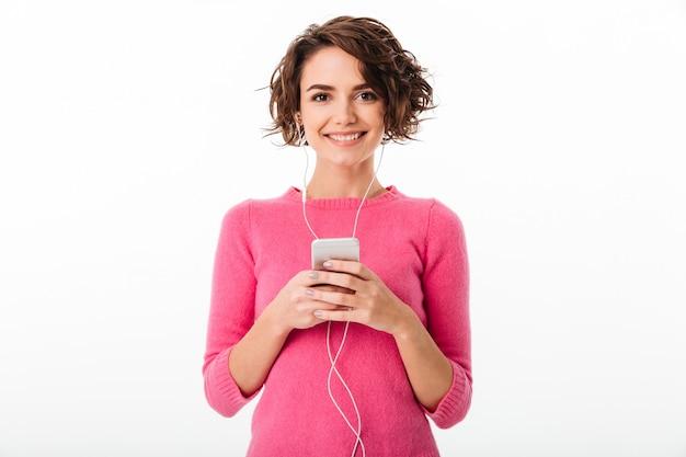 Portret van een vrolijk mooi meisje dat aan muziek luistert
