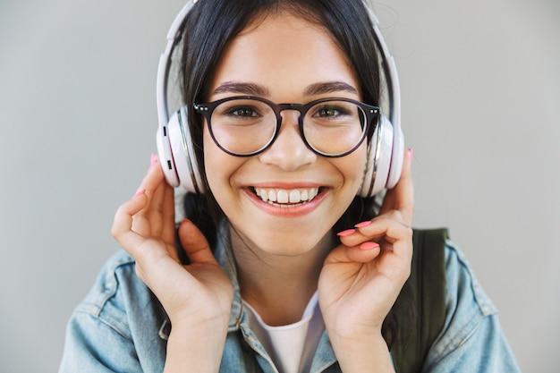 Portret van een vrolijk mooi meisje in een spijkerjasje met een bril geïsoleerd over een grijze muur die muziek luistert met een koptelefoon.