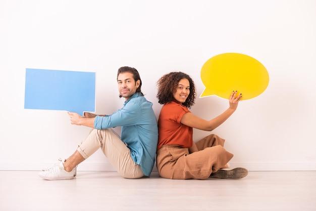 Portret van een vrolijk multi-etnisch paar dat rug aan rug op vloer zit en dialoogtags vasthoudt tijdens het uitwisselen van online berichten