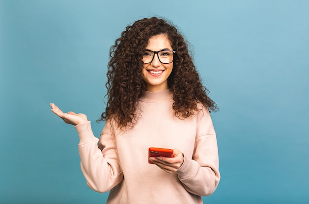 Portret van een vrolijk ongedwongen krullend meisje dat een mobiele telefoon houdt en haar vinger richt vanaf geïsoleerd op blauwe achtergrond.