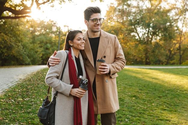Portret van een vrolijk paar man en vrouw 20s die afhaalkoffie drinken uit papieren bekers tijdens het wandelen in het herfstpark