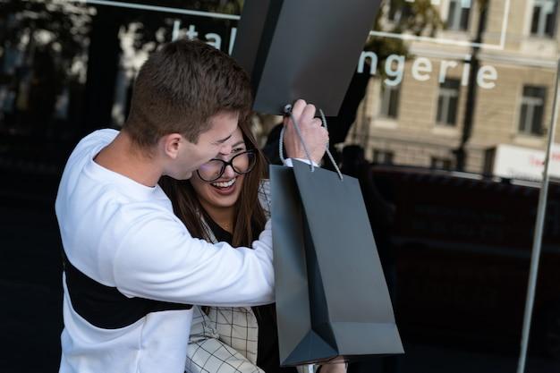 Portret van een vrolijk stel met boodschappentassen veel plezier. vrolijke jongen en meisje na succesvol winkelen.