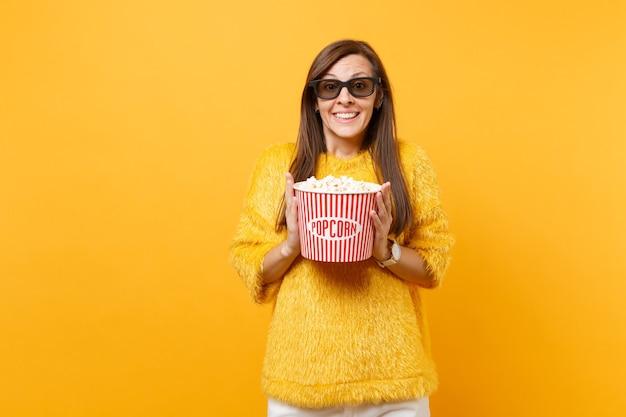 Portret van een vrolijk vrij jong meisje in een bonttrui, een 3d imax-bril die naar een film kijkt met een emmer popcorn geïsoleerd op een felgele achtergrond. mensen oprechte emoties in de bioscoop, levensstijl.